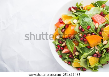 Fresh salad with fruits and greens on white paper background top view with space for text. Healthy food. - stock photo
