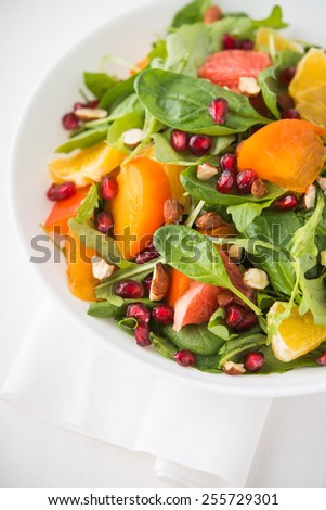 Fresh salad with fruits and greens on white wooden background close up. Healthy food.
