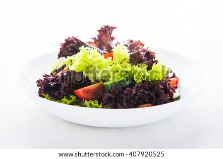 Fresh salad with green and purple lettuce, tomatoes and cucumbers on white wooden background close up. Healthy food. - stock photo