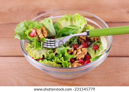 Fresh salad with greens, garnet and spices on plate on table close-up - stock photo