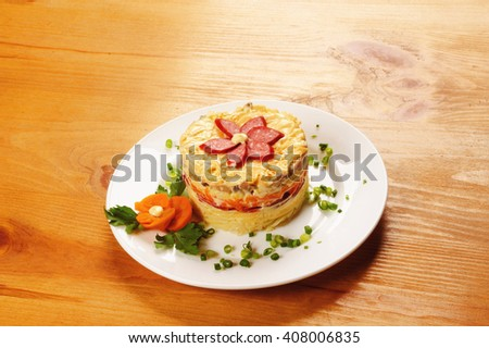 Fresh salad with mayonnaise, sausage,  potatoes, pepper on wooden table - stock photo