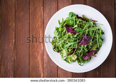 Fresh salad with mixed greens (arugula, mesclun, mache) on wooden background top view. Space for text. Healthy food. - stock photo