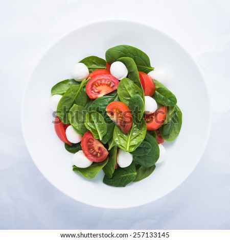 Fresh salad with mozzarella cheese, tomato and spinach on white paper background top view. Healthy food. - stock photo