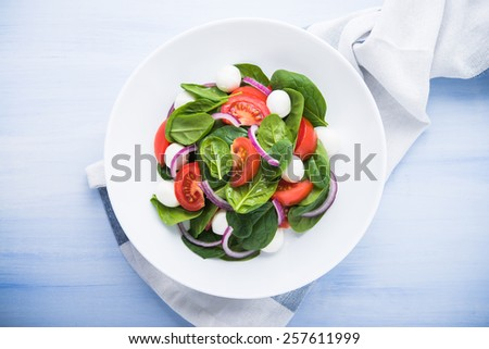 Fresh salad with mozzarella cheese, tomato, spinach and purple onion on blue wooden background top view. Healthy food. - stock photo