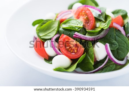 Fresh salad with mozzarella cheese, tomato, spinach and purple onion on white background close up. Healthy food. - stock photo