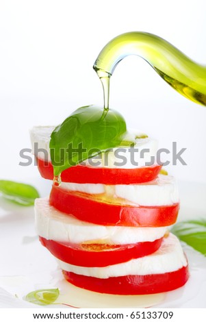 Fresh salad with mozzarella, tomato and basil with olive oil pouring from bottle - stock photo