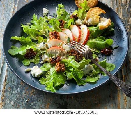 Fresh salad with pear, gorgonzola cheese and caramelized walnuts - stock photo
