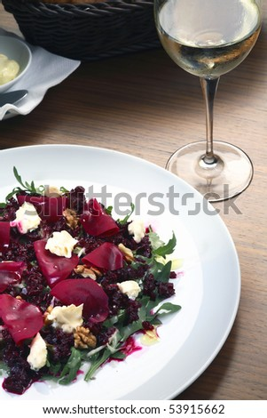Fresh salad with prosciutto,various vegetables and  tartar sauce  in restaurant setting with white wine - stock photo