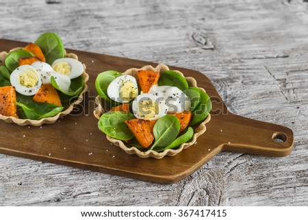 Fresh salad with roasted pumpkin, spinach and quail eggs served in tartlets from whole wheat flour. - stock photo