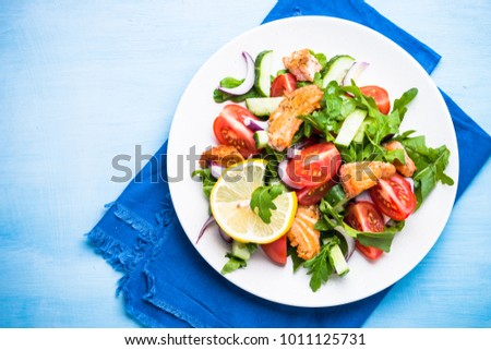 Fresh salad with salmon, arugula, tomatoes, cucumber and onion. Top view on blue table. Diet healthy food.