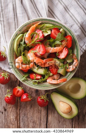 Fresh salad with shrimp, avocado and strawberry close-up on the table. Vertical view from above - stock photo