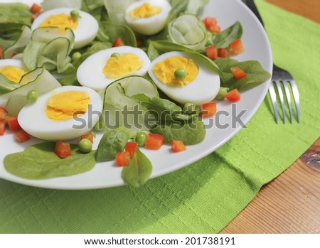 Fresh salad with spinach,eggs,cucumber and peas - stock photo