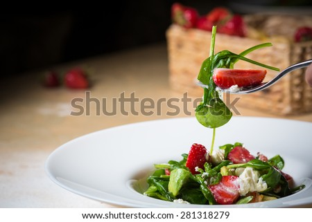 Fresh Salad with strawberries, goat cheese and shrimps dressed with balsamic vinegar and olive oil - stock photo