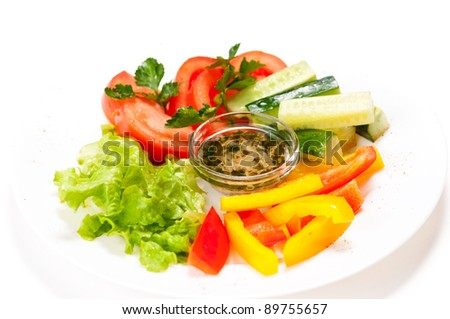 Fresh salad with tomaoto, cucumber, lettuce and pepper on plate isolated on white