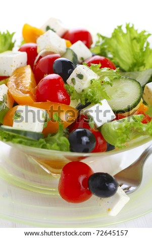 Fresh salad with tomato, cucumber and olives closeup