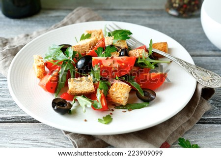 Fresh salad with tomatoes and croutons on a plate, food - stock photo