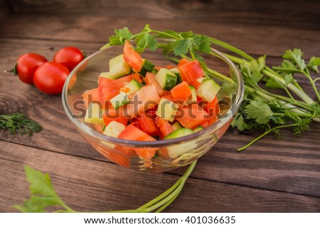 Fresh salad with tomatoes and cucumber on a wooden background in a transparent plate. - stock photo
