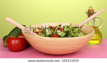 Fresh salad with tomatoes and cucumbers on green background - stock photo
