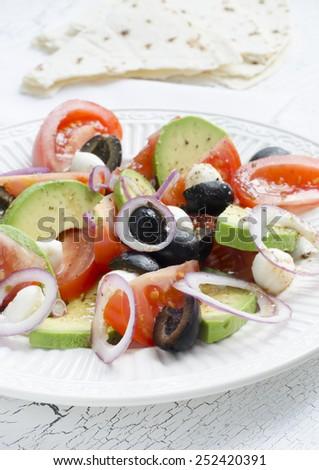 Fresh salad with tomatoes, avocado, mozzarella and black olives. - stock photo