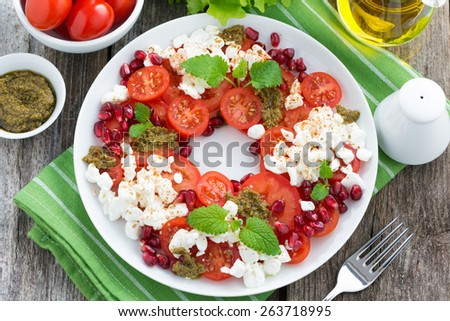 fresh salad with tomatoes, cottage cheese, pesto and pomegranate, top view, horizontal - stock photo
