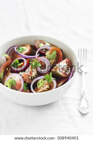 fresh salad with tomatoes in a white bowl on a white surface