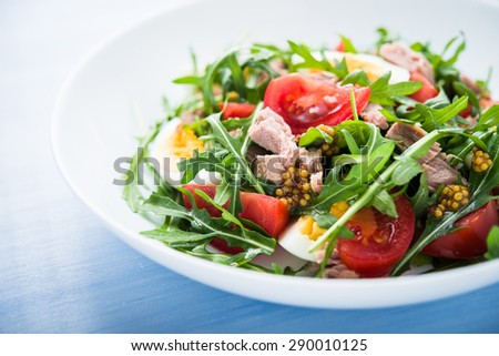 Fresh salad with tuna, tomatoes, eggs, arugula and mustard on blue wooden background close up. Healthy food. - stock photo