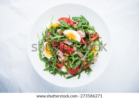 Fresh salad with tuna, tomatoes, eggs, arugula and mustard on white textured background top view. Healthy food. - stock photo