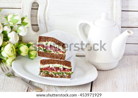 Fresh salami sandwiches with vegetables wrapped in paper.