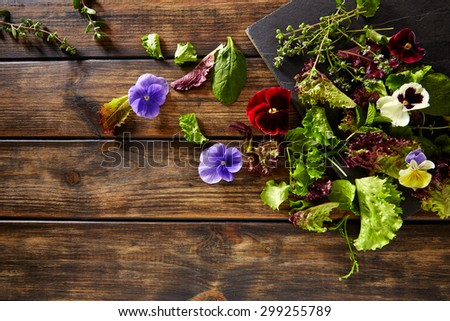 Fresh saland ingredients lettuce flowers spinach on rustic wood - stock photo