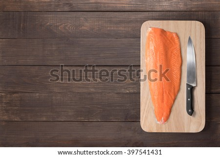 Fresh salmon and knife on cutting board on the wooden table. Top view. - stock photo