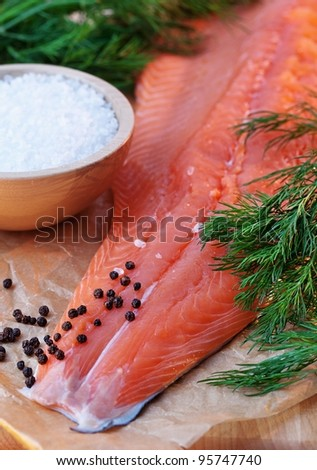 fresh salmon filet with ingredients : salt, dill, black pepper. - stock photo