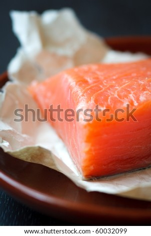 Fresh salmon fillet on the brown plate,shallow focus - stock photo
