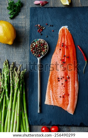 Fresh salmon fillet with asparagus and aromatic herbs, spices and vegetables - healthy food, diet or cooking concept. Top view. - stock photo