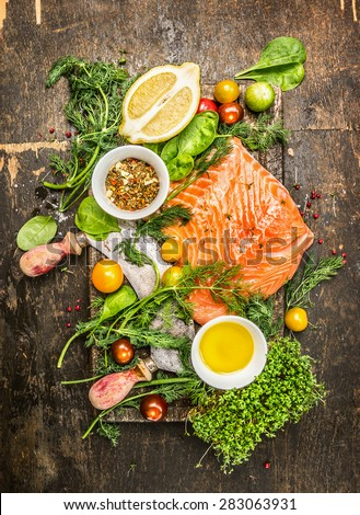 fresh salmon fillet with fresh healthy herbs,vegetables, oil and spices on rustic wooden background, top view - stock photo