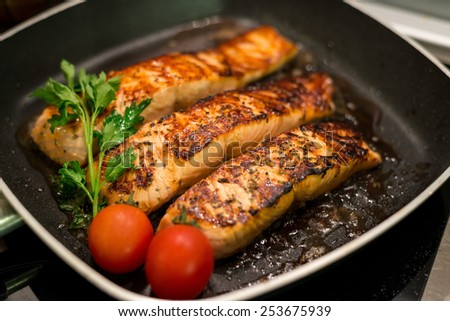 Fresh salmon fillets grilled in a pan - stock photo