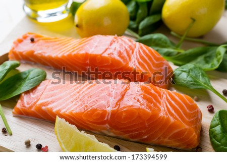 Fresh Salmon Steaks with Lemons and Baby  Spinach  on a Cutting Board - stock photo