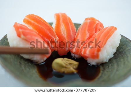 Fresh salmon sushi on ceramic plate with chopsticks, Japanese style
