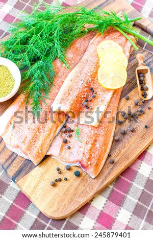 Fresh salmon/trout in marinade with seasoning on wooden cutting board- ready to eat, ready to cook. Indoors close-up. - stock photo