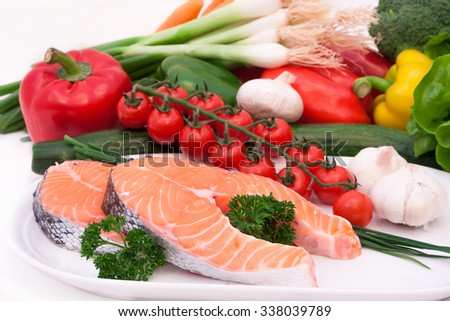 fresh salom fillet with a composition of raw vegetables on white