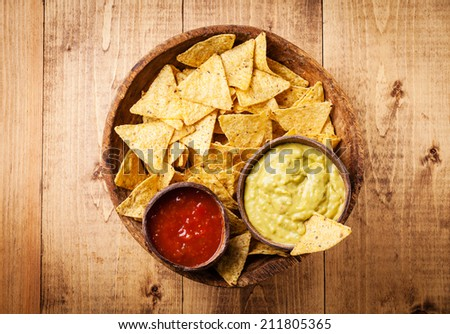Fresh salsa and guacamole dips with nachos chips on wooden background - stock photo