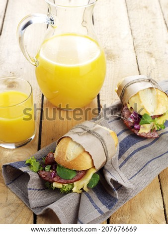 Fresh sandwich with salami and cheese and glass of orange juice - stock photo