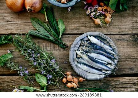 Fresh sardines. Fish with vegetables. Mediterranean fish on plate - stock photo