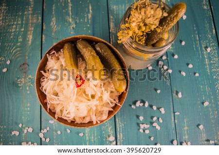Fresh sauerkraut and pickles. At the turquoise wooden background. Top view. - stock photo