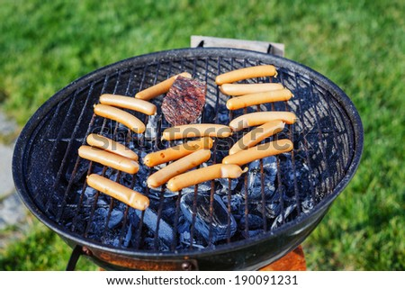 Fresh sausage and hot dogs grilling outdoors on a barbecue grill. - stock photo