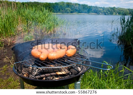Fresh sausage preparing on grill at the lakeshore - stock photo