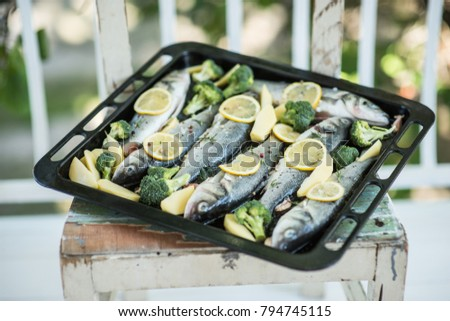 Fresh sea bass with lemon and broccoli in baking tray