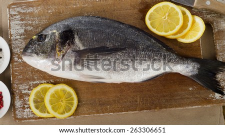 Fresh sea bream with lemon on  wooden cutting board. - stock photo