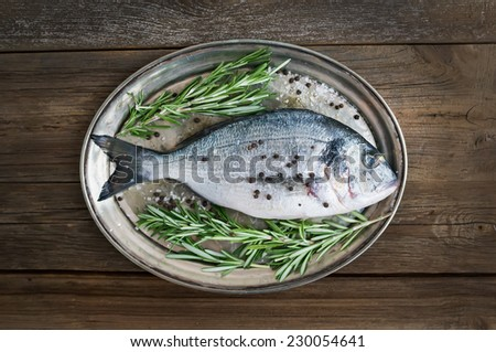 Fresh sea fish (sea bream) on a metal dish with rosemary and spices ready for cooking over a rustic wood background - stock photo