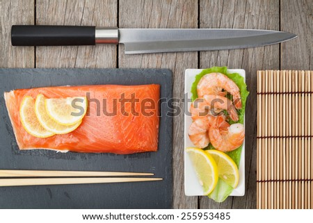 Fresh sea food and kitchen utensils on wooden table - stock photo
