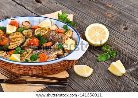 fresh seabass baked with vegetables on wooden table - stock photo
